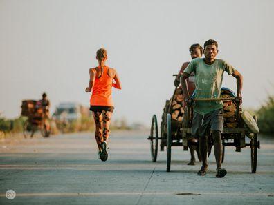 Samantha Gash running past a man pulling a rickshaw in India.