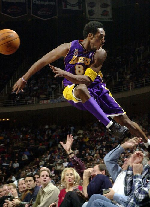 In this 2001 photo Los Angeles Lakers' Kobe Bryant jumps over a row of fans after saving the ball from going out of bounds.