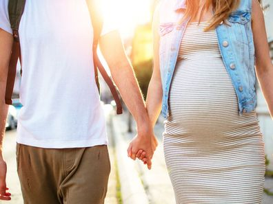 Man walking hand in hand with pregnant partner