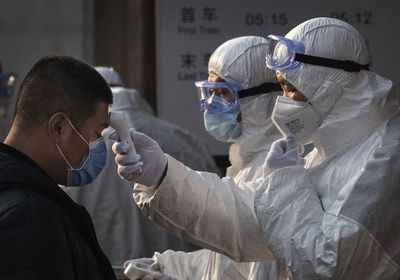 Health workers check vitals of people entering a subway in China