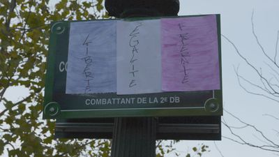 A hand-drawn Tricolour flag adorns a sign in the Place de la Republique. (Jack Hawke, 9News.com.au)