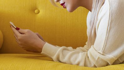 Woman on lounge looking at phone texts