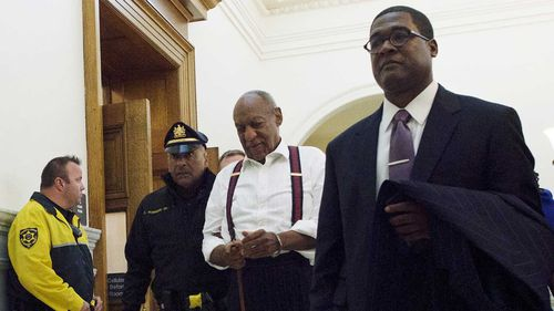 Bill Cosby is led out of court in handcuffs.