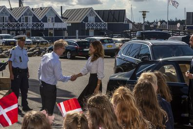 Princess Mary shakes hands with host during royal engagement.