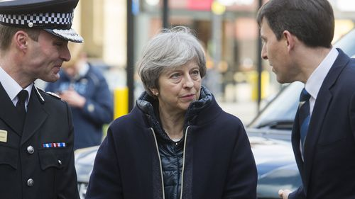 Britain's Prime Minister Theresa May, centre, is briefed by members of the police as she views the area where former Russian double agent Sergei Skripal and his daughter were found critically ill, in Salisbury, England,