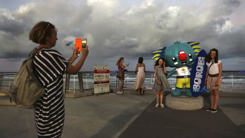 Children pose for the photographs with Commonwealth Games mascot Borobi at Surfers Paradise Beach as clouds linger behind them. (AAP)