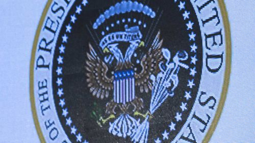 The seal showed a two-headed eagle clutching golf clubs and money, instead of arrows and an olive branch. The stars on the American shield were replaced with USSR-style hammers and sickles.