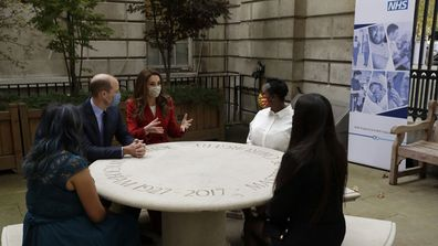 Prince William and his wife Kate the Duchess of Cambridge meet pharmacist Joyce Duah, second right, and pharmacy technicians Amelia Chowdhury, right, and Dipal Samuel, left, as they visit St. Bartholomew's Hospital in London, to mark the launch of the nationwide 'Hold Still' community photography project, Tuesday, Oct. 20, 2020
