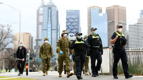 Police and the Australian military patrol the banks of the Yarra River in Melbourne, Australia. Face masks or face coverings are now mandatory for anyone leaving their homes in the Melbourne metropolitan area or the Mitchell Shire.