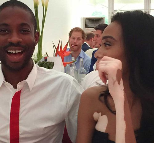 Tongue-poking Prince Harry photobombs model