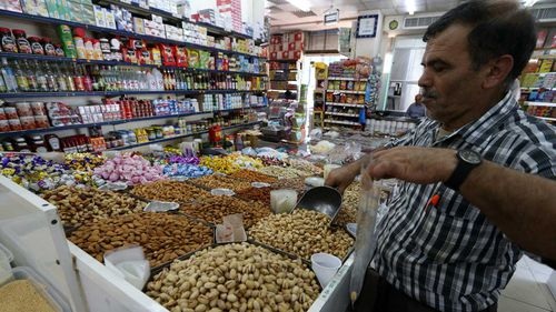 A shopper weights Iranian pistachios at a popular market in Abu Dhabi, United Arab Emirates. (AAP)