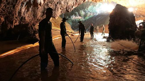 Thai rescue teams arrange a water pumping system at the entrance to the flooded cave complex. Picture: AAP
