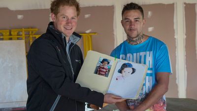 But it has not been all military might for the prince. <br> Here, Prince Harry meets Zeb King and looks at a drawing of his son, during his visit to Odyssey House, a residential drugs and alcohol rehab centre in Christchurch. (AAP)