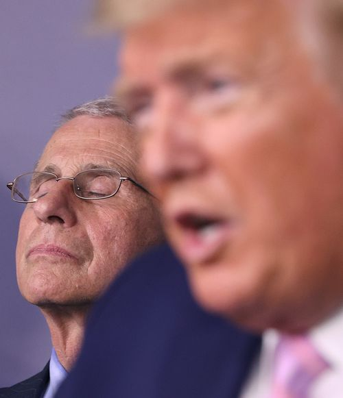 Dr Anthony Fauci listens to President Donald Trump