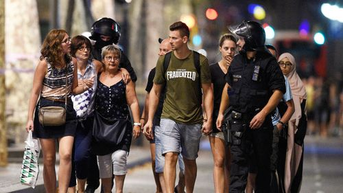 People are escorted by Spanish policemen outside a cordoned off area after a van ploughed into the crowd, killing 13 persons and injuring over 80 on Las Ramblas in Barcelona on August 17, 2017. (AFP)