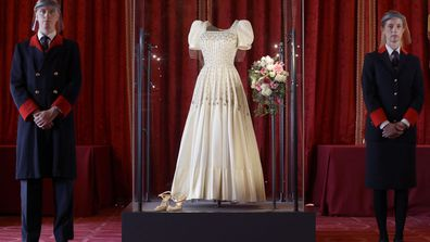 Two wardens stand by Princess Beatrice's wedding dress, designed by the renowned British fashion designer Sir Norman Hartnell and loaned to by Queen Elizabeth II, on display at Windsor Castle in Windsor, England, Wednesday, Sept. 23, 2020