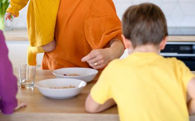 Woman giving children breakfast