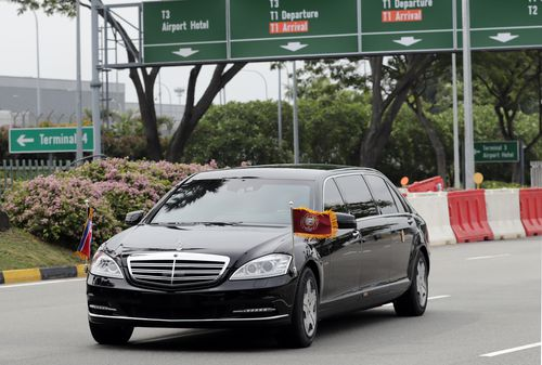 North Korean leader Kim Jong-un is driven in car with flags flying as the motorcade heads out of Singapore Airport.