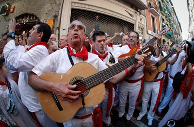 Musicians play on the sidelines as people try to outrun the bulls