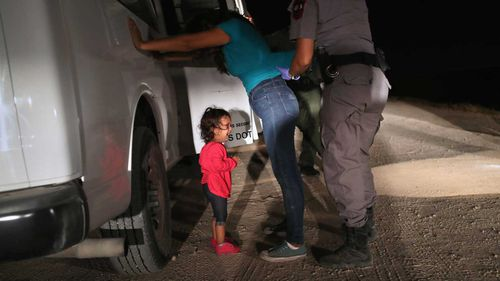 A two-year-old Honduran asylum seeker cries as her mother is searched and detained in Texas. (Getty)