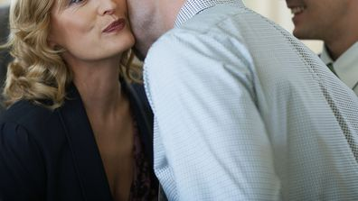 Should men and women greet each other with a kiss or a hug in the office
