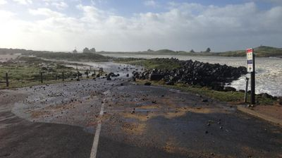 Powerful winds and 7m waves have sent rocks rolling across a road in Port Fairy. (Twitter)