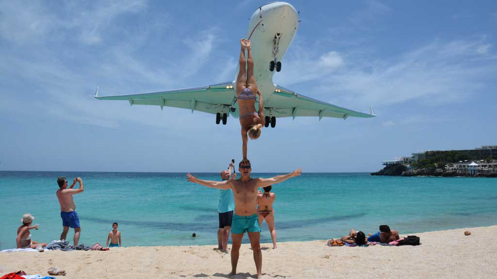 Couple perform daring stunt as low-flying plane passes on famous beach. Photo: SWNS/Mega