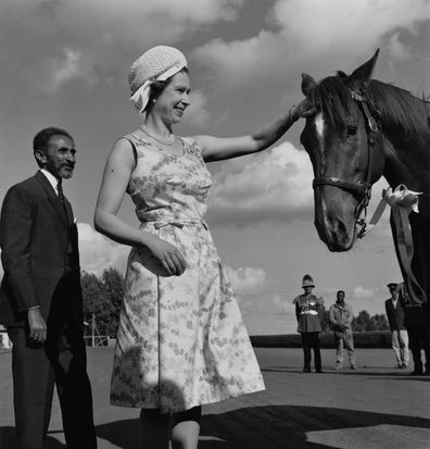 Queen Elizabeth II pats the head of a horse, watched by Emperor Haile Selassie (1892 - 1975) during her royal tour of Ethiopia, February 1965.