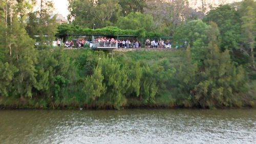 An anxious crowd looks on over the river where the man's body was eventually found.