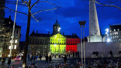 The Royal Palace at Dam Square in Amsterdam, is seen with the black, yellow and red colours of the Belgian flag. (AAP)