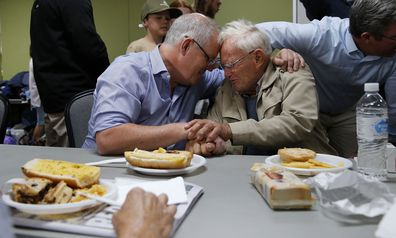 Prime Minister Scott Morrison is seen comforting 85-year-old Owen Whalan of Half Chain road in Koorainghat Sunday, November 10, 2019. (AAP Image/Darren Pateman) NO ARCHIVING