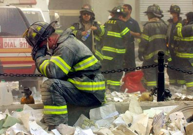 Exhausted firefighter Gerard McGibbon, of Engine 283 in Brownsville, Brooklyn, prays after the World Trade Center buildings collapsed.