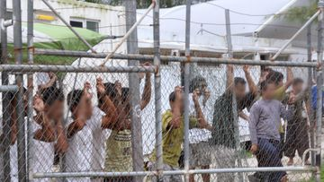 Asylum seekers stand behind a fence at the Manus Island detention centre in Papua New Guinea in 2014. (AAP file image)