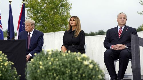 President Donald Trump, first lady Melania Trump and Interior Secretary David Bernhardt sit on stage at the 19th anniversary observance of the Sept. 11 terror attacks, at the Flight 93 National Memorial in Shanksville, Pa., Friday, Sept. 11, 2020
