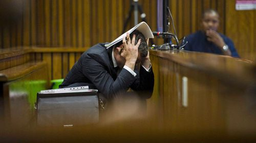 Oscar Pistorius grabs his head in shock as images of a bloodied Reeva Steenkamp are shown at his murder trial in Pretoria High Court. (Getty)