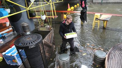 A worker clears out stock in a flooded riverside cafe. (AAP)