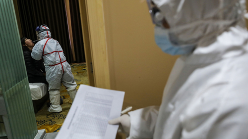 This photo taken on February 4, 2020 shows a medical staff member (L) taking samples from a person to be tested for the new coronavirus at a quarantine zone in Wuhan, the epicentre of the outbreak, in China's central Hubei province. . (Photo by STR / AFP) / China OUT (Photo by STR/A