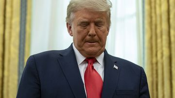 President Donald Trump listens during a ceremony to present the Presidential Medal of Freedom to former football coach Lou Holtz, in the Oval Office of the White House, Thursday, Dec. 3, 2020, in Washington