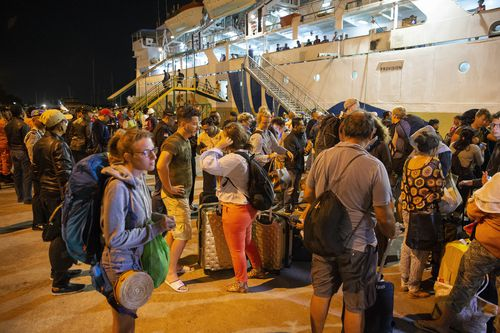 Thousands of tourists have been left to fend for themselves, seeking out boats away from the island or staying in the Lombok Airport. Picture: AAP.