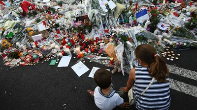 Children sit next to flowers and candles placed in the road for victims of the deadly Bastille Day attack. Source: AFP