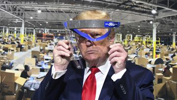 President Donald Trump looks through a face shield while touring Ford Motor Co.'s Rawsonville Components Plant in Michigan.
