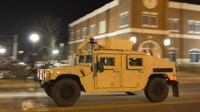 A National Guard Humvee roars through the centre of Ferguson. (Getty Images)