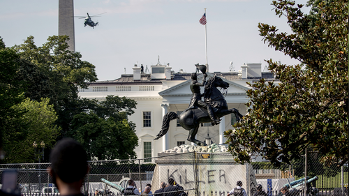A presidential helicopter, the Washington Monument, and the White House are visible behind a statue of Andrew Jackson in Lafayette Park with the word Killer spray painted on its base after protesters tried to topple the statue near Black Lives Matter Plaza, Tuesday, June 23, 2020, in Washington. (AP Photo/Andrew Harnik)