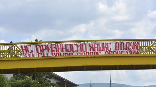 """A banner reading """"We don't recognize decisions of the Hague"""" in Serbian Cyrillic letters hangs off a pedestrian overpass on a street in Banja Luka, Bosnia and Herzegovina, Tuesday, June 8, 2021. UN appeals judges on Tuesday, June 8, 2021 upheld the conviction of former Bosnian Serb military chief Ratko Mladic for genocide and other offenses during Bosnia's 1992-95 war and confirmed his life sentence. (AP Photo/Radivoje Pavicic)"""