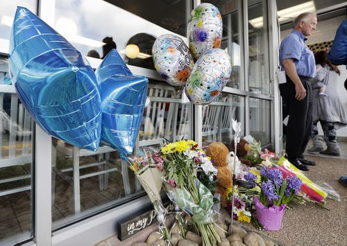 Tributes for the victims outside the store. (AP/AAP)