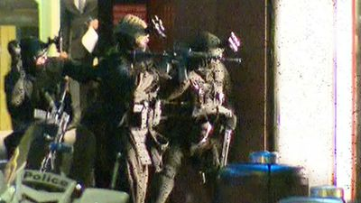 The bright lights of stun grenades illuminated the cafe as multiple rounds of gunfire echoed down the street. (9NEWS)