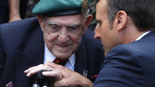 French President Emmanuel Macron holds the hand of French war veteran Leon Gautier, a member of the Kieffer commando.