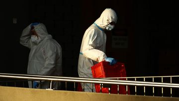 Workers wearing personal protective equipment are seen outside the Flemington Tower Public Housing Complex.
