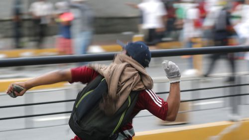 People riot during a protest against President Maduro as Juan Guaido, President of the Venezuelan Parliament, announces that he assumes executive powers, in Caracas, Venezuela.