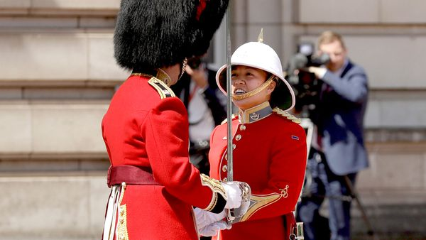 Canadian Captain Megan Couto, right, makes history by becoming the first female Captain of the Queen's Guard as she takes part in the Changing the Guard ceremony at Buckingham Palace in London. (AAP)
